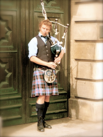 A street performer plays the bagpipe on the Royal Mile.