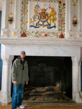 Tyler standing in front of the fireplace inside the Great Hall.