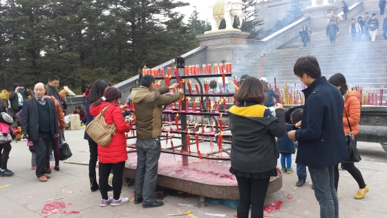 People lighting incense at the base of the statue