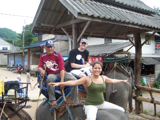 Riding on the elephants head.